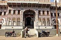 A caretaker walks into the haveli that he helps to maintain.