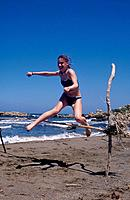 Beach,sand. High jump. Young girl jumping over sticks in frame.
