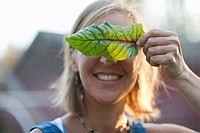 Smiling woman holding leaf in front of her face