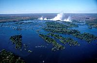 Zambezi river above waterfalls. Islands in water. Mist rising from casade of water. Rainbow in air. Aerial.