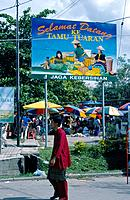 Island of Borneo. Market. Sign. Umbrellas over market stalls.