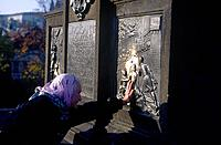 Charles Bridge. Place to make a wish. Old woman placing hand on image relief.