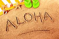 The word Aloha written on a sandy beach, with flip flops, towel, starfish and seashells in the background. Sharp focus on Aloha and distant objects sl...