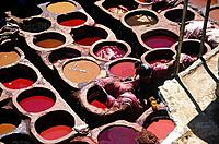 Tanneries quarter. Rooftop dyeing pits. Vats of coloured liquid dye. Red,orange. Skins,fabric to be dyed.