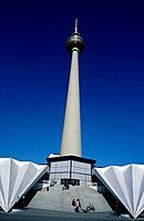 Alexanderplatz. Television tower. Tall white round tower. Steps. People.