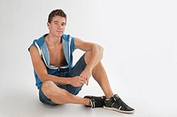 Full-body photograph of a teenage boy sitting, in short jeans and sleeveless blue vest.