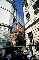 Nikolaikirke. Church with thin spires. View from street level. Cafe. People seated.