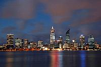 Skyline of Perth across the river Swan at night with passing clouds.