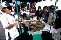 Plaza Principale city square. A food stall with two women making tacos for sale.