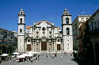 Cathedral facade. Large bell towers. Market square. Stalls,people.
