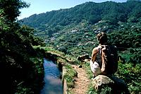 Woman with rucksack sitting looking over man made water channel and terraced hillsides.