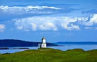 Cattle Point Lighthouse on San Juan Island, WA USA, on Spring day with large clouds.