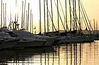 Sunset over yachts and motor boats moored in the Alghero marina with reflections on the water