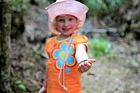 Young girl holding a stick insect and smiling at the Rimutaka forest park in New Zealand. Children like exploring.