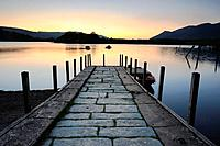 Wide angle view along jetty at sunset over Derwent Water, Keswick, Lake District National Park, Cumbria, England, UK.