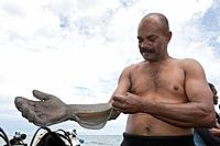 Shark feeder prepares itself with Chain Gloves, Beqa Lagoon, Viti Levu, Fiji