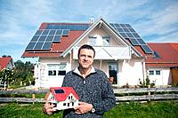 Mature man holding miniature house in front of house with solar panels