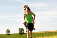 Young couple piggyback riding in field