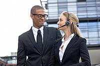 Young businesspeople with headset outdoors