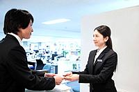 Receptionists Receiving Businesscard From Businessman