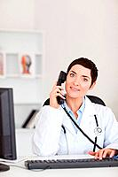 Portrait of a smiling female doctor making a phone call in her office