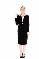 Charming female in suit pointing at a copy space while standing against a white background