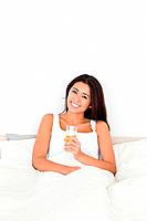 brunette woman holding orange juice sitting in bed looking into camera in bedroom