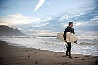 a young man carries his surfboard down the beach, la push washington united states of america