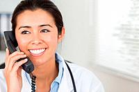 Attractive female doctor on the phone and posing in her office