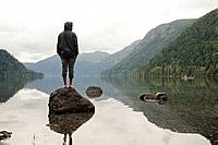 a young man stands on a rock looking out over cameron lake, british columbia canada