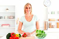Woman standing in kitchen with vegetables
