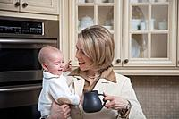 a businesswoman holding her baby in the kitchen at home, jordan ontario canada
