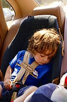 A child in a car seat in a car sleeping