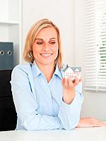 Gorgeous blonde businesswoman showing miniature house looking at it in her office