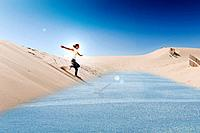 a young woman slides on a board over the punta paloma sand dunes into the water, tarifa cadiz andalusia spain