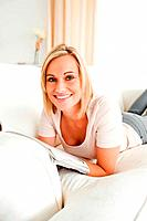 Blond_haired woman with a magazine in her living room