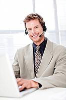Businessman in headset using laptop