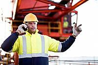 Worker using walkie talkie on oil rig