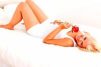 Calm woman smelling a flower while lying on her bed