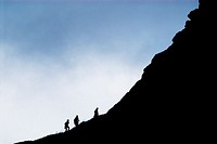 Silhouette of hikers on mountain ridge, Lofoten islands, Norway