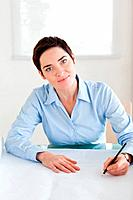 Charming woman with a architectural plan looking into the camera in an office