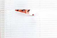 Brunette businesswoman peeking out of a window in an office