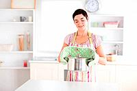 Cute Woman holding a pot in a kitchen