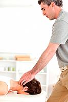 A masseur is massaging a female customers neck
