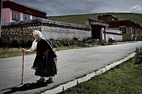 Old woman walk on the road. Litang city. China country