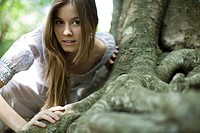 Young woman leaning on roots of tree