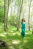 Young woman running through woods