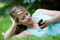 Woman texting on her cell phone while relaxing on the lawn
