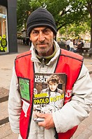 A Big Issue vendor selling the Big Issue magazine in Norwich , Norfolk , England , Britain , Uk