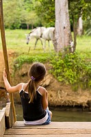 Costa Rican girl watching horses graze along the Sierpe River in Costa Rica